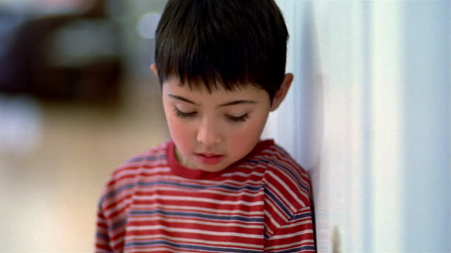 close up sad male child looking down and sighing / looking up at cam / looking down - tristezza video stock e b–roll