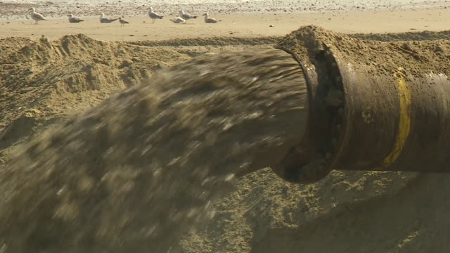vidéos et rushes de close up sand and water being pumped onto norfolk beach at bacton for sandscaping project to save eroding stretch of coastline - érodé