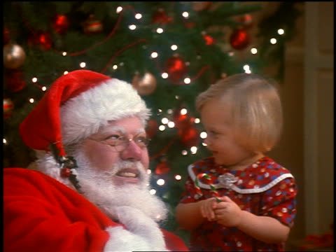 close up santa claus + small girl holding candy cane singing with christmas tree in background - candy cane stock videos & royalty-free footage
