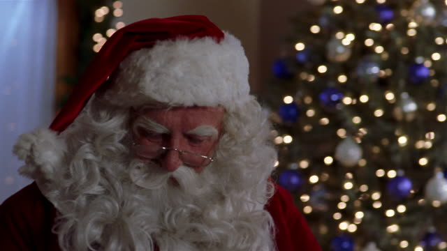 close up santa claus turning head while placing gifts under christmas tree / hushing at cam / mexico city - silenzio video stock e b–roll