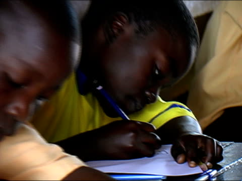 Close up schoolchildren writing/ zoom out wide shot children in classroom/ Ghana