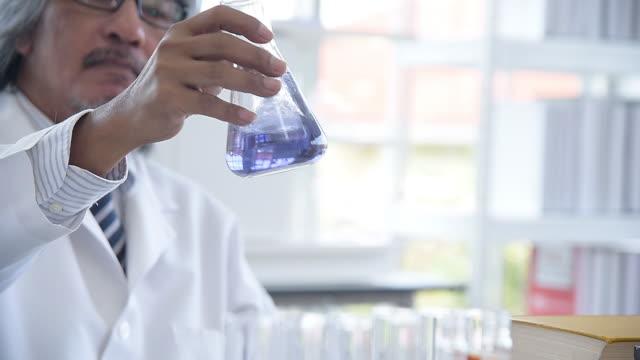Stäng upp forskare man testa någon lösning i bägare