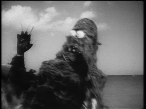 b/w 1961 close up pan sea monster with claws attacking man near ocean - モンスター点の映像素材/bロール