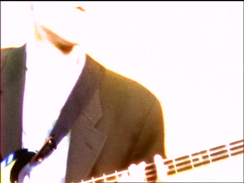 close up seated man's hands playing bass guitar in studio / tilt up to face tilt down - music video stock videos & royalty-free footage