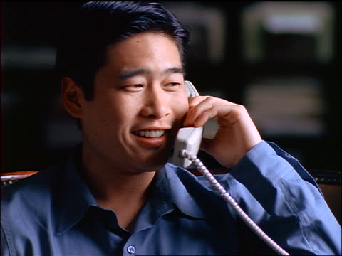 close up seated young asian man talking + laughing on telephone - one mid adult man only stock videos & royalty-free footage