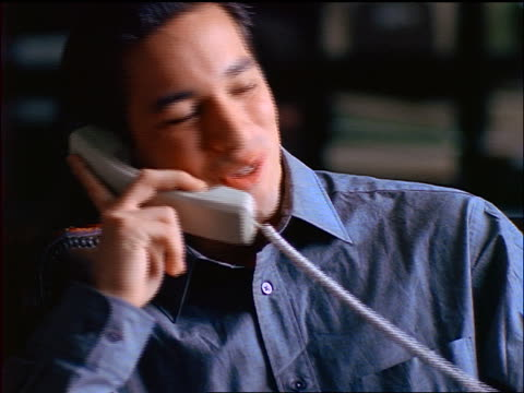 close up seated young man talking on telephone - 若い男性だけ点の映像素材/bロール
