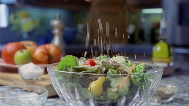 close up seeds being sprinkled and dressing being poured on salad in glass bowl / tossing salad - salad bowl stock videos & royalty-free footage