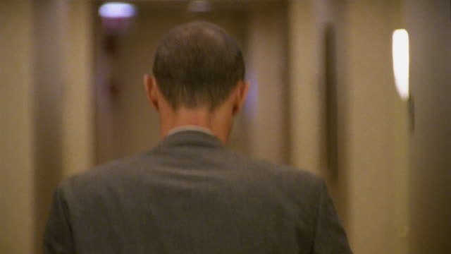 Close up selective focus man walking down hotel hallway