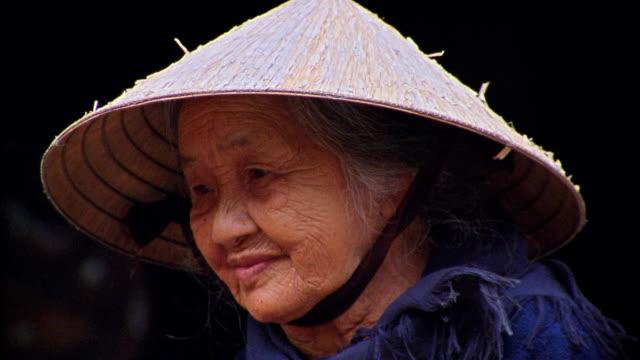 Close up senior Asian woman wearing straw hat / Hoi An, Vietnam