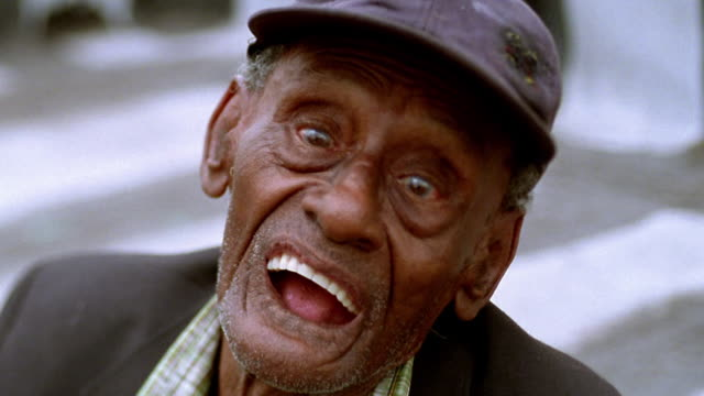 close up senior black man in hat putting in bottom dentures and making face outdoors / los angeles - ugliness stock videos and b-roll footage