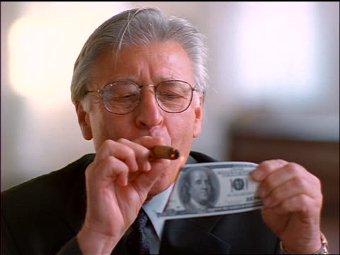 close up senior businessman in eyeglasses lighting cigar with burning $100 bill + laughing - greed stock videos and b-roll footage