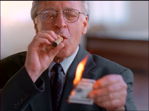 close up senior businessman in eyeglasses lighting cigar with burning $100 bill + laughing