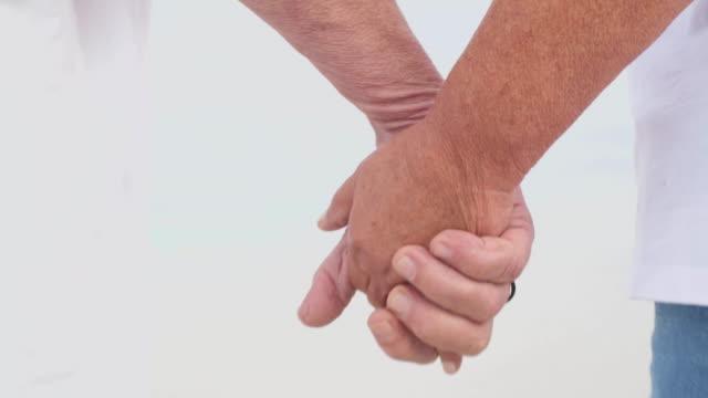 vídeos de stock, filmes e b-roll de feche-se casal sênior de mãos dadas prestes a andar por uma linda praia branca - braço humano