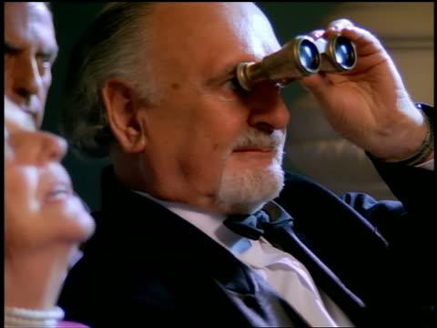vidéos et rushes de close up senior couple in formalwear sharing binoculars at event - smoking