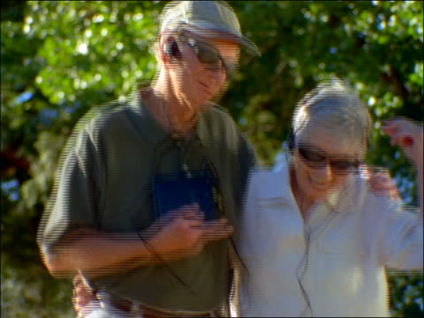 close up senior couple in sunglasses + headphones dancing outdoors - personal stereo stock videos & royalty-free footage