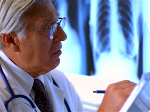 close up PAN senior male doctor with eyeglasses looking at x-rays + writing notes
