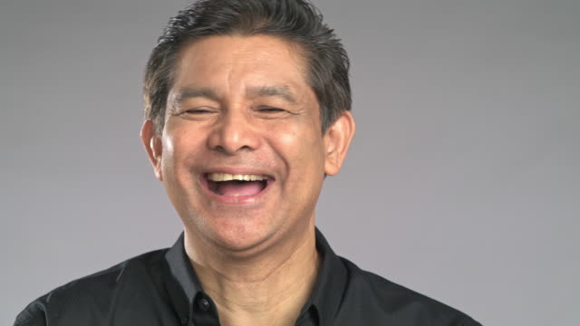 close up senior man big laughing isolated in grey background. asian man in black shirt. - black shirt stock videos & royalty-free footage