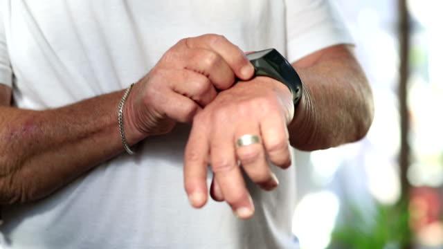 vídeos de stock e filmes b-roll de close up senior man checks smart watch after exercise - computador utilizável como acessório