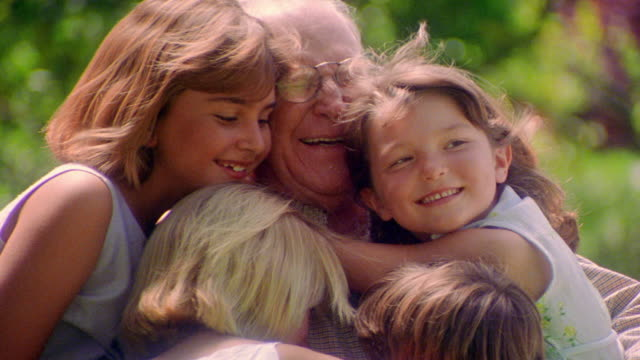 close up senior man in eyeglasses surrounded by children hugging him + smiling outdoors / zoom in - 数人点の映像素材/bロール