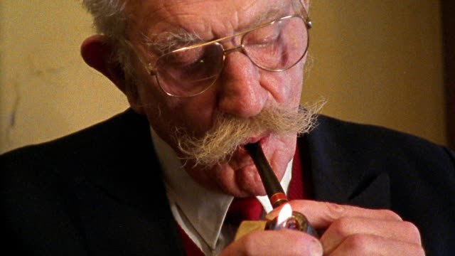 close up senior man lighting and smoking pipe - moustache stock videos and b-roll footage