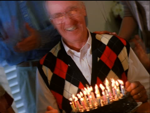 CANTED close up senior man making wish + blowing out candles / senior woman kisses him