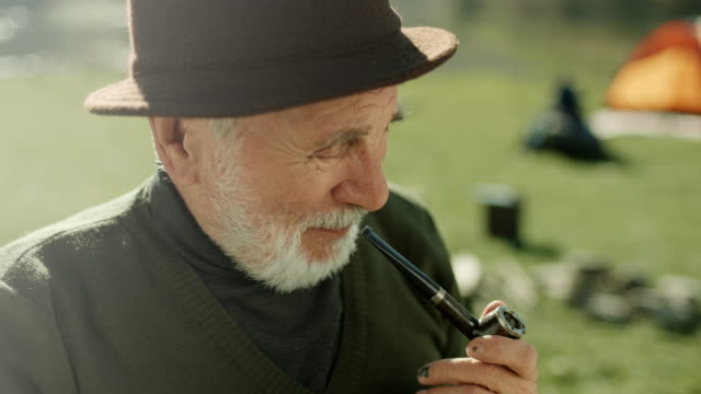 Close up, senior man smoking pipe and looking down