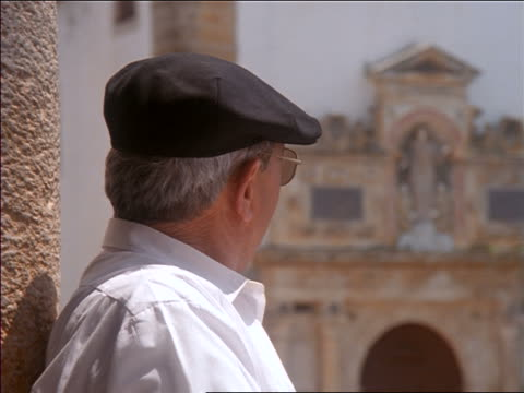 close up senior man standing in front of church + smiling at camera / Oridos, Portugal