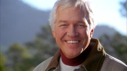 close up senior man turning and smiling at cam outdoors - 50 54 år bildbanksvideor och videomaterial från bakom kulisserna