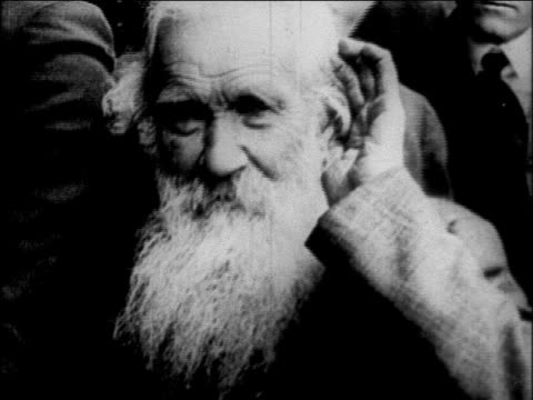 b/w 1927 close up senior man with beard holding hand to ear / newsreel - deafness stock videos & royalty-free footage