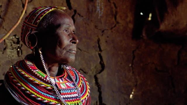 close up senior masai tribeswoman looking off-camera / kenya - masai stock videos and b-roll footage