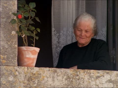close up senior woman in black leaning out of window of home / Oridos, Portugal
