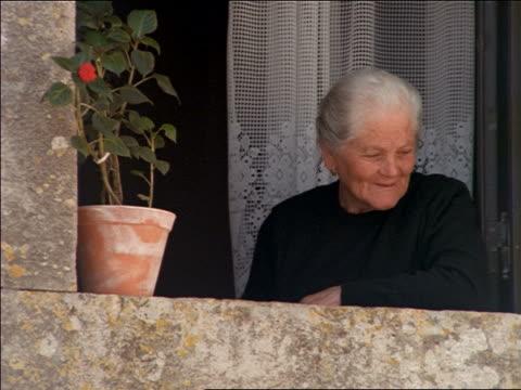 vídeos de stock, filmes e b-roll de close up senior woman in black leaning out of window of home / oridos, portugal - peitoril de janela