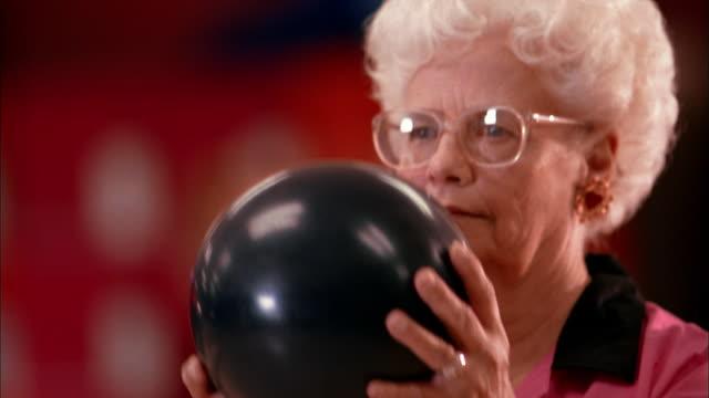 stockvideo's en b-roll-footage met close up senior woman in team jersey bowling - bowlen