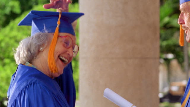 close up pan senior woman receiving diploma from man outdoors + adjusting tassle / both wear caps + gowns - cap stock videos & royalty-free footage