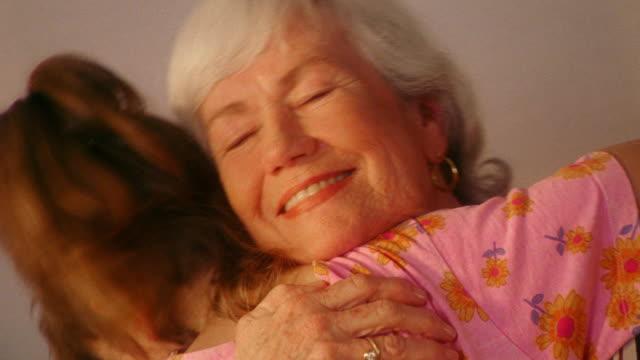 close up senior woman smiling + hugging REAR VIEW girl