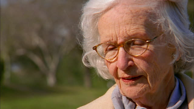 close up senior woman turning and smiling at cam outdoors - only senior women stock videos & royalty-free footage