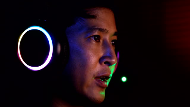 close up serious asian esport player playing video games with his headset. - gamer stock videos & royalty-free footage