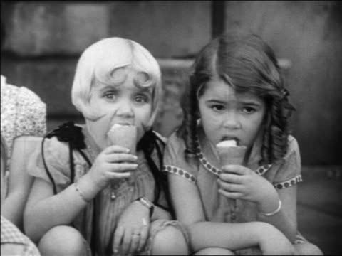 b/w 1931 close up shirley jean + dorothy from our gang sitting + eating ice cream cones / feature - 1931 stock videos & royalty-free footage
