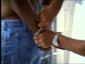 vidéos et rushes de close up shirtless black man being handcuffed + led away - injustice