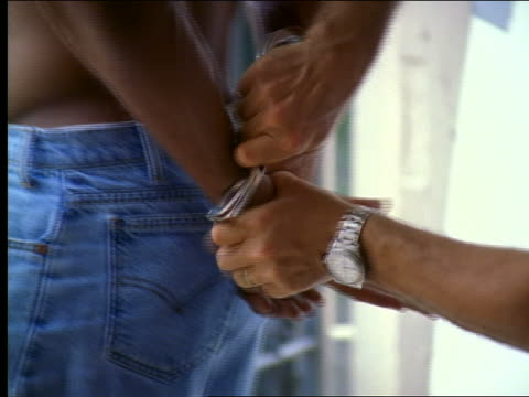 close up shirtless Black man being handcuffed + led away