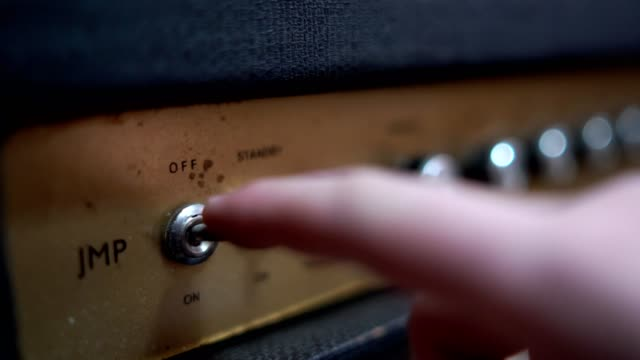 close up shoot of a hand turning on retro guitar amplifier. - rock group stock videos & royalty-free footage