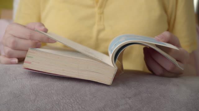 Nahaufnahme Schuss asiatische Frau beim Lesen eines Buches bei ihr zu Hause lernen