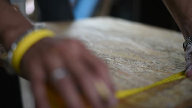close up shot carpenter measures wood with measure tape. - tape measure stock videos & royalty-free footage