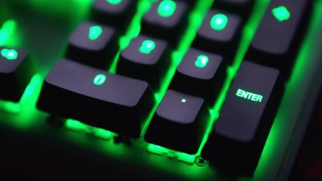 vídeos y material grabado en eventos de stock de de cerca del dedo de disparo está presionando la tecla enter en el teclado con luz led verde. - pulsar