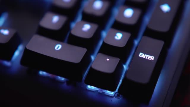 close up shot finger is pressing enter key on keyboard with light blue led light. - enter key stock videos & royalty-free footage