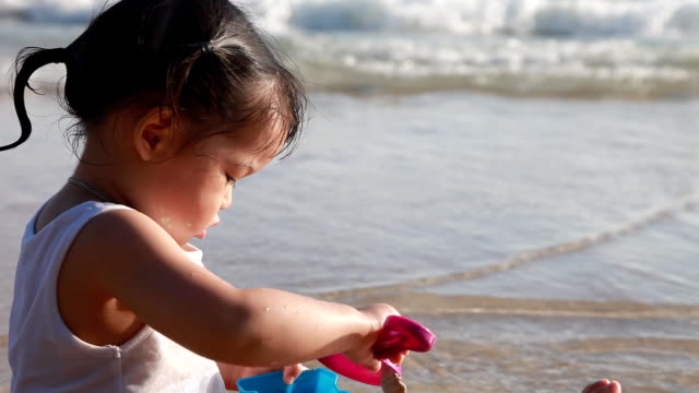 Close up shot girl with her toy on the beach