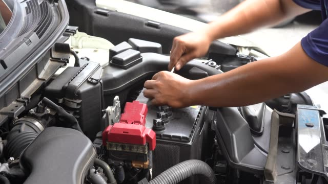 Close-up shot handen van monteur los en draai een pet van de auto batterij voor het gieten van gedistilleerd water Refill power onderhoud