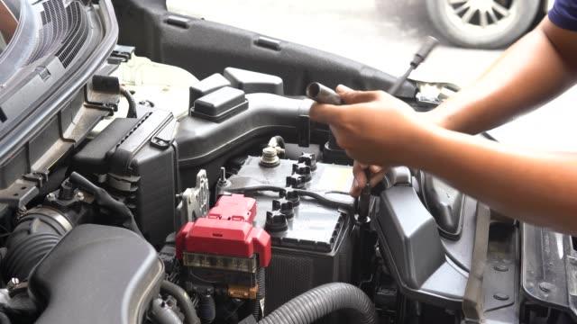 närbild sköt händerna på mekaniker lossa och dra åt ett tak av bil batteri försörjning för att hälla destillerat vatten påfyllning makt underhåll - batteri bildbanksvideor och videomaterial från bakom kulisserna