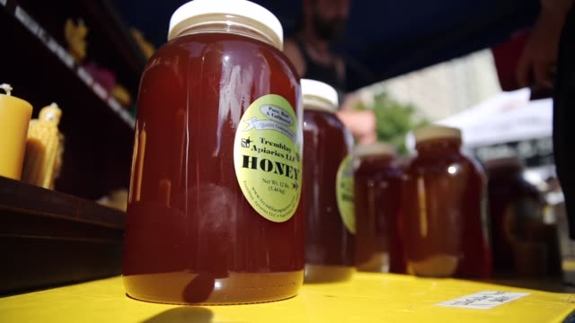vídeos y material grabado en eventos de stock de close up shot jar of honey shoppers visit the greenmarket at union square park new york city's largest farmers market with up to 140 vendors selling... - jarra