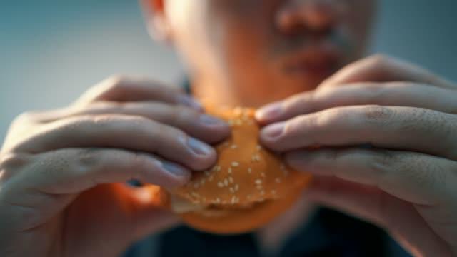 クローズアップショット男性はハンバーガーを食べています。喜んで - unhealthy eating点の映像素材/bロール